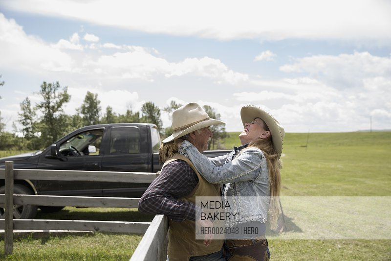 Laughing rancher couple hugging at rural fence