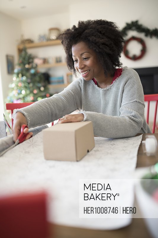 Smiling woman wrapping Christmas gifts at table