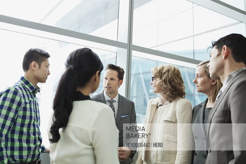 Group of business people talking together in office building