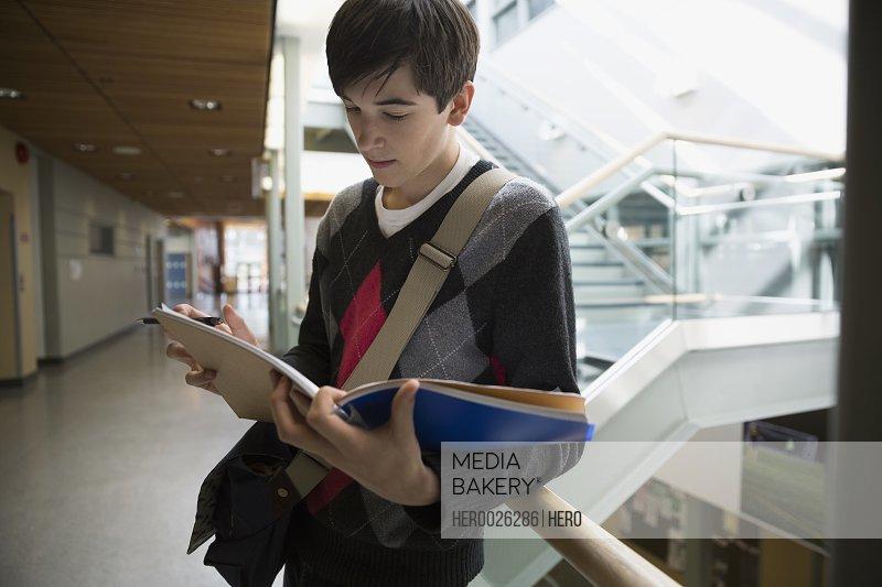 High school student reviewing notes in school corridor