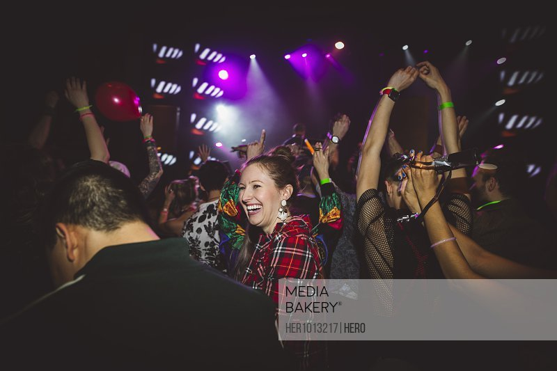 Female millennial laughing, partying and dancing in nightclub