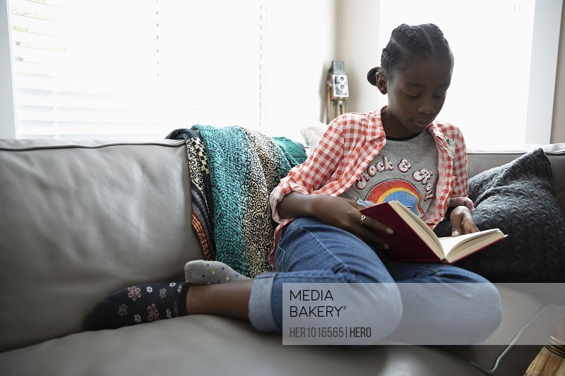 Tween girl reading book on living room sofa