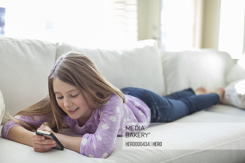 Young girl text messaging with mobile phone lying on sofa
