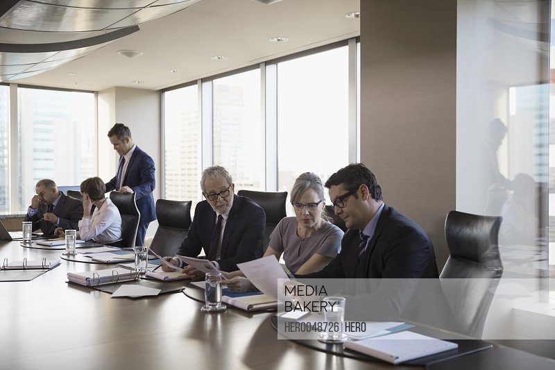 Lawyers discussing paperwork in conference room meeting