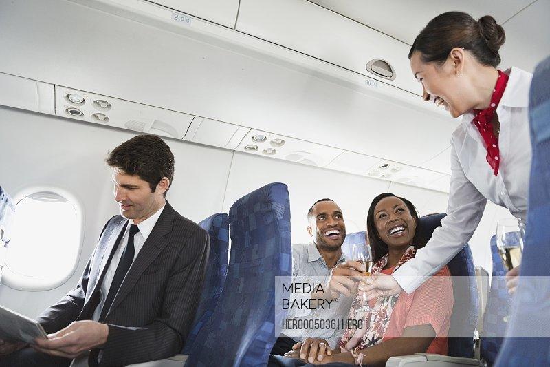 Smiling flight attendant serving drinks to passengers
