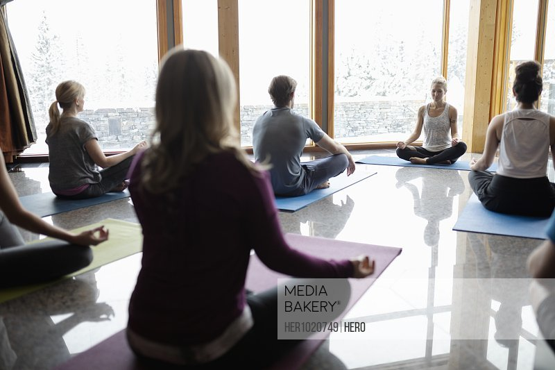 Instructor leading yoga class sitting in lotus position in studio