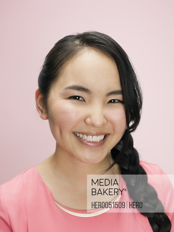 Portrait smiling young Asian woman with long black braid against white background