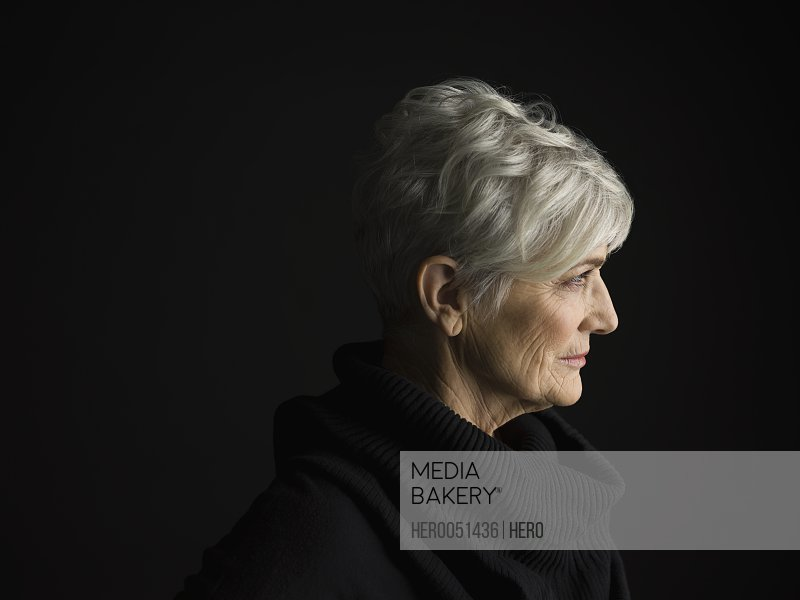 Profile portrait senior woman with short gray hair looking away against black background