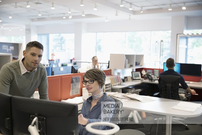 Businessman and businesswoman using computer in open plan office