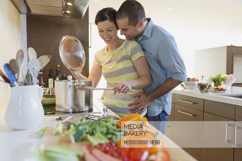 Husband cuddling wife as she prepares dinner
