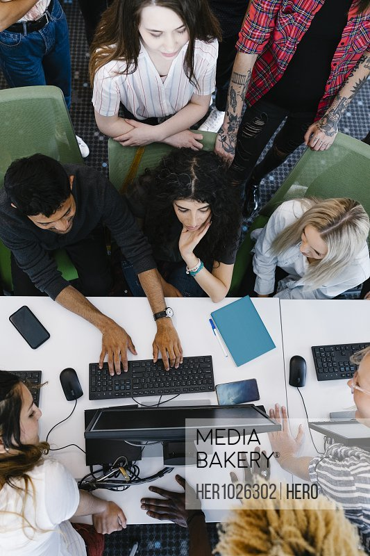 Overhead view of university students using computer
