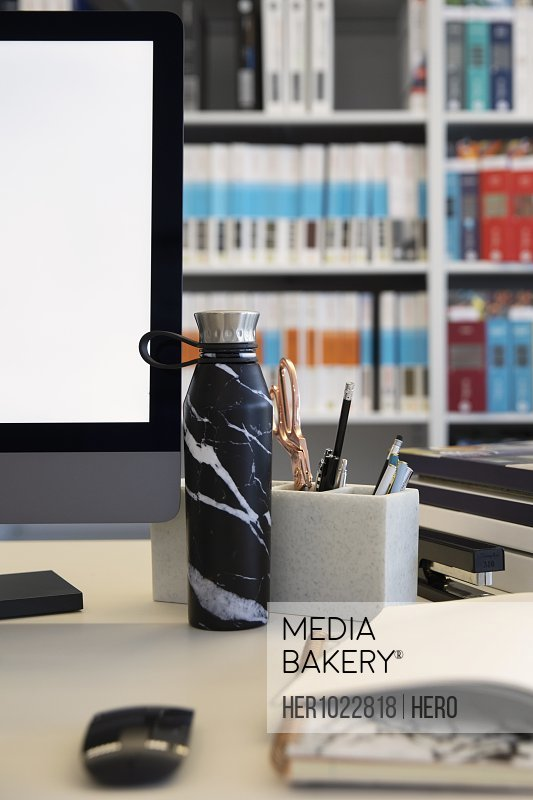 Water bottle on desk next to computer in office