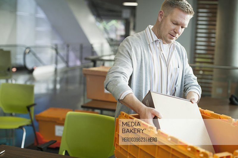 Businessman unpacking computer hardware from box