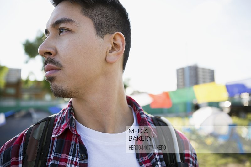 Close up portrait pensive young man with black hair looking away at summer music festival campsite