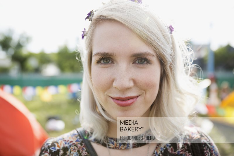 Close up portrait young blonde woman at summer music festival campsite