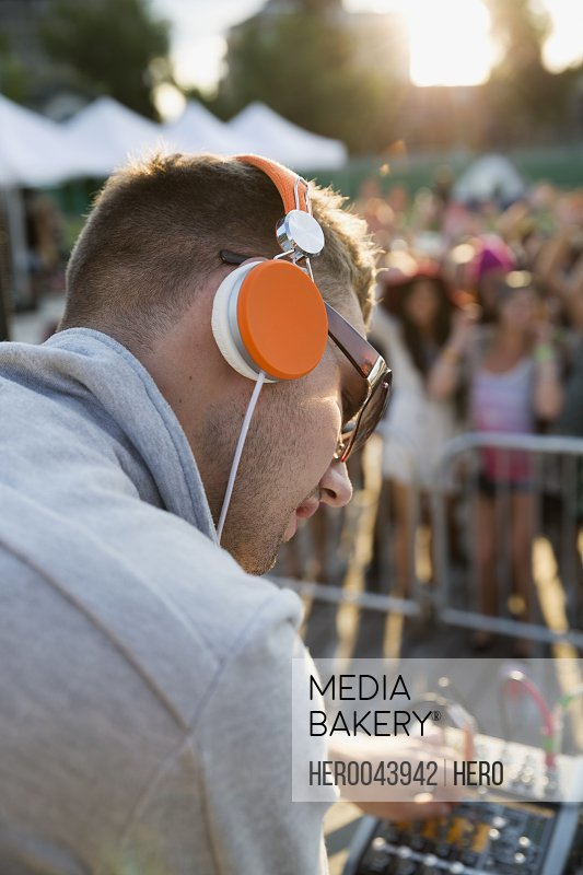 Close up DJ with headphones adjusting equipment on stage at summer music festival