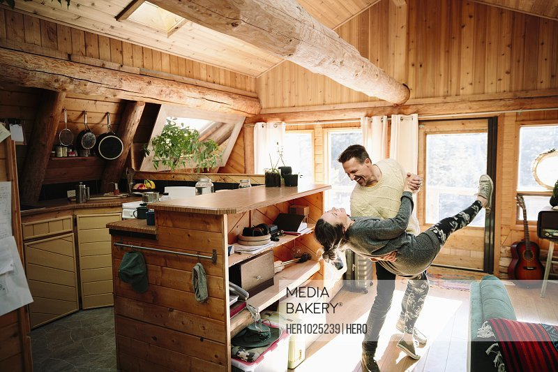 Playful couple dancing in cabin