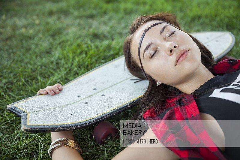 Teenage girl sleeping on skateboard in grass
