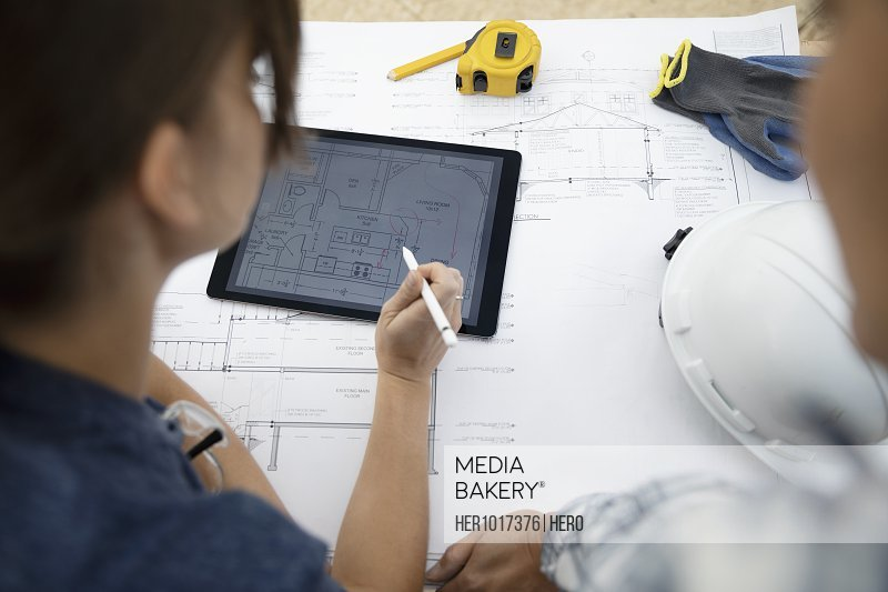 Female architect volunteers reviewing blueprints and using digital tablet, building house