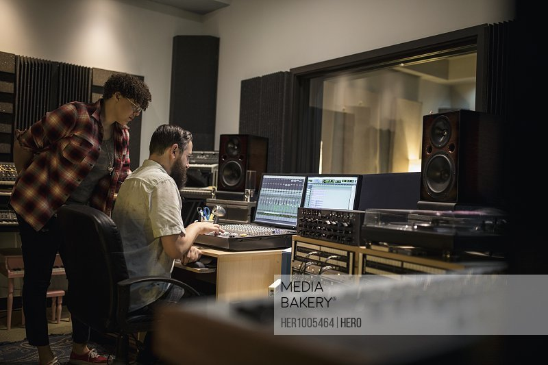 Music producers working at sound mixer in recording studio