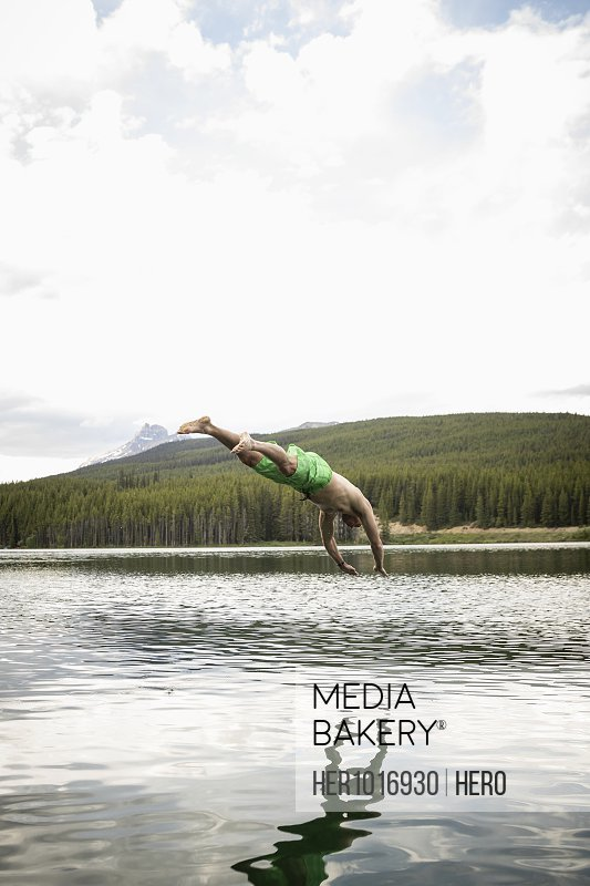 Mature man diving into lake, Alberta, Canada