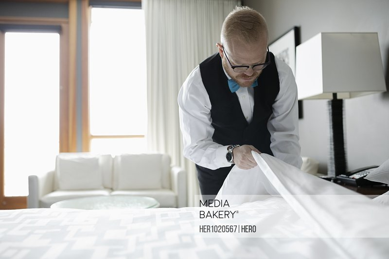 Dedicated male room service hotel staff housekeeper making bed in hotel room