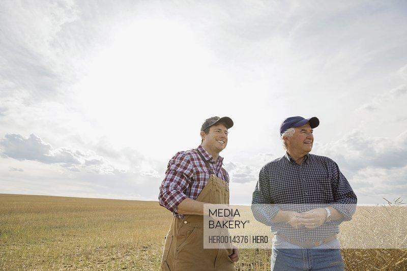 Farmers standing in sunny wheat field
