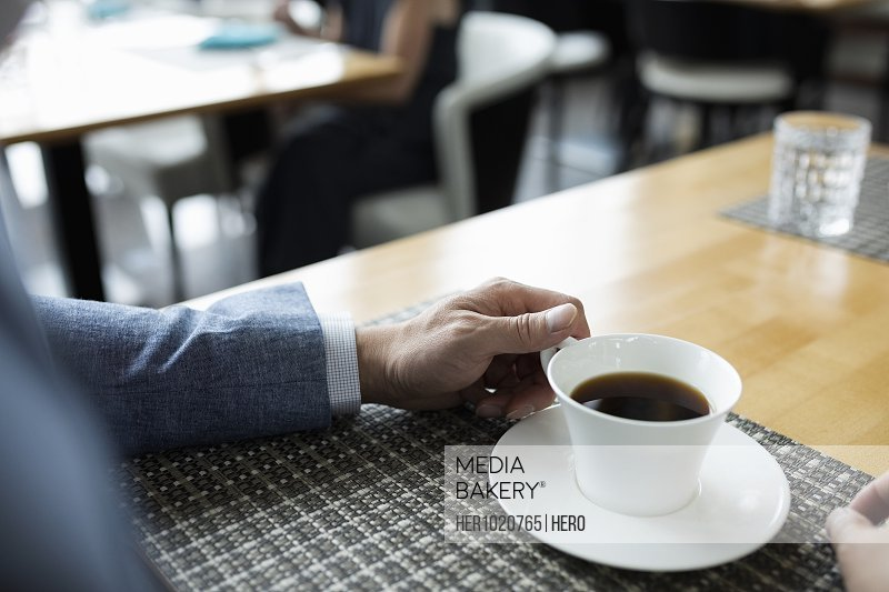 Close up businessman drinking coffee at cafe table