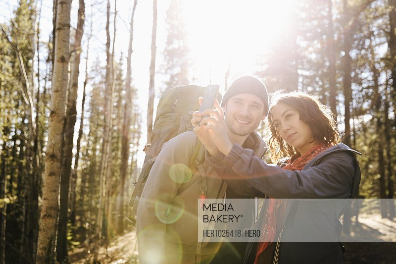 Couple taking selfie, hiking in sunny woods