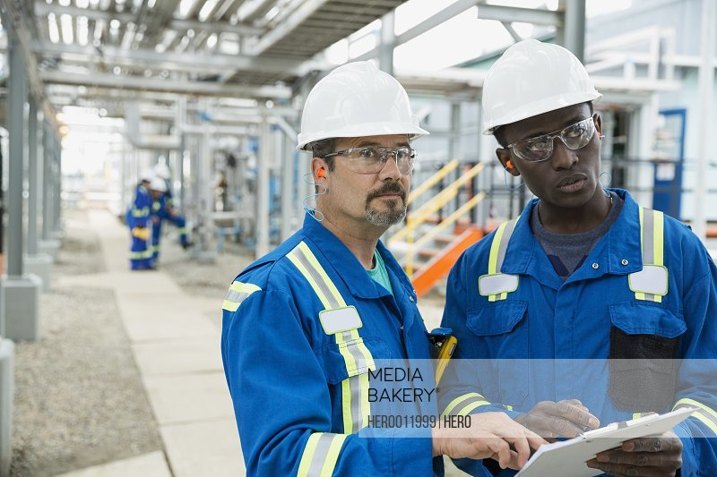Male workers reviewing paperwork at gas plant