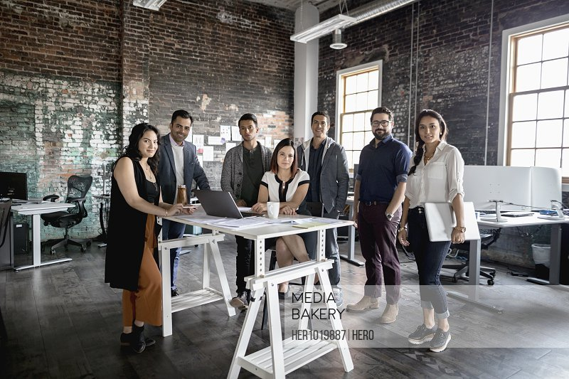 Portrait confident creative business people meeting in open plan loft office