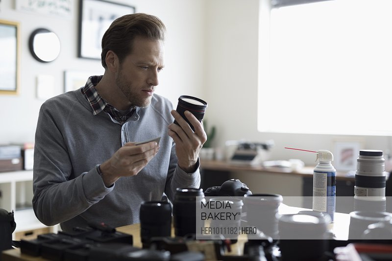 Focused male photographer cleaning camera lenses