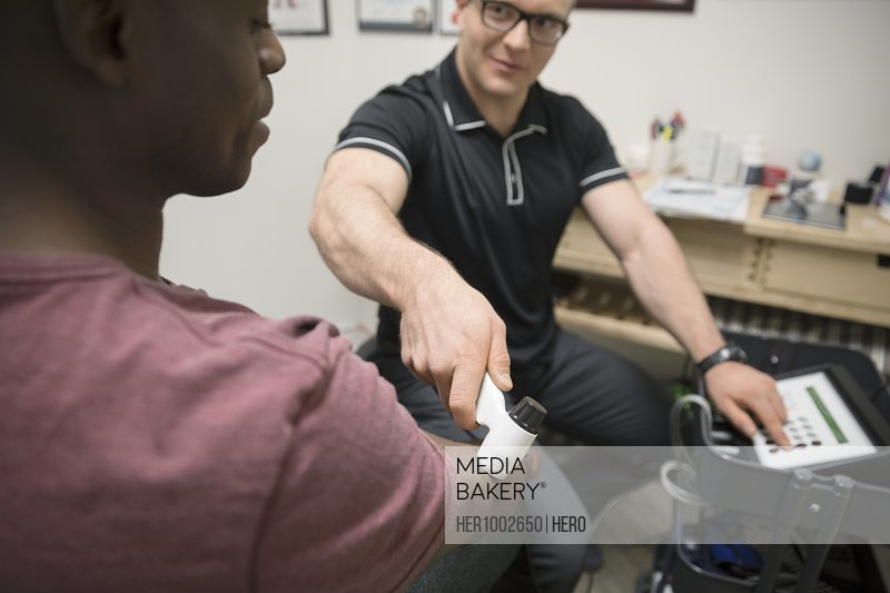Male physiotherapist using ultrasound machine on client in office