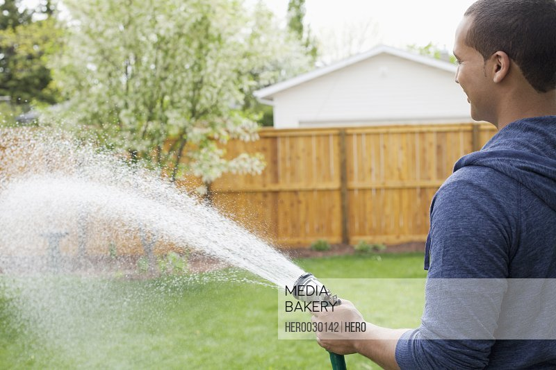 young homeowner watering the lawn