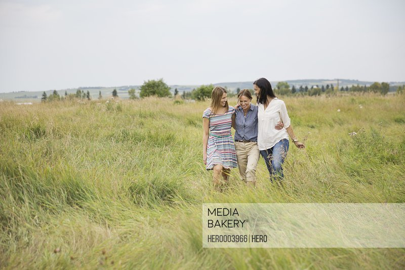 Affectionate female family members walking through field