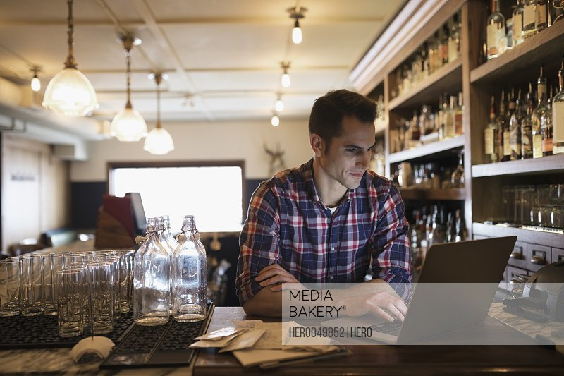 Male business owner using laptop at bar