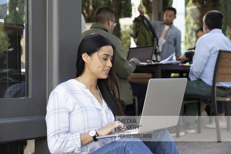 Businesswoman using laptop at sidewalk cafe