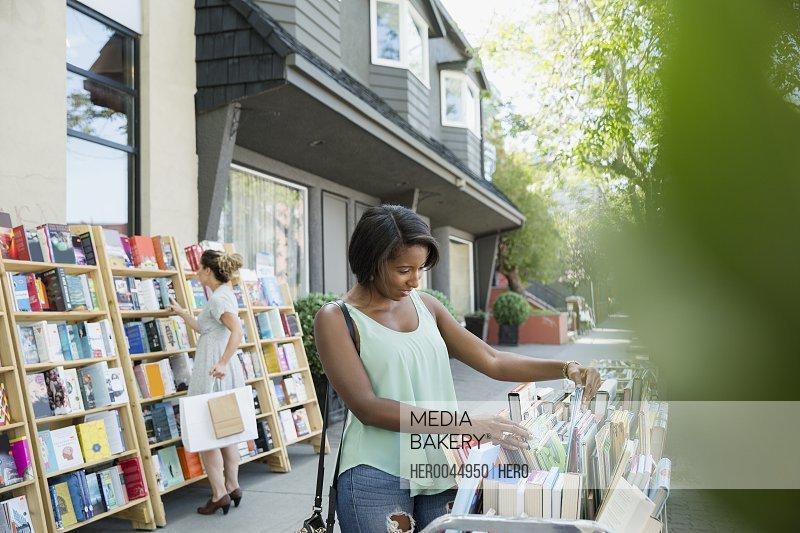 Woman browsing books at bookstore storefront sidewalk bin