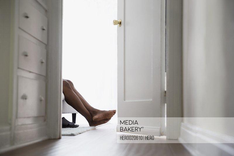 Bare feet of man in bedroom doorway