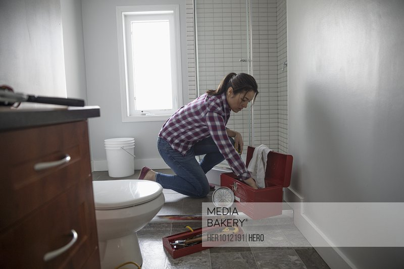 Woman with toolbox repairing shower, DIY