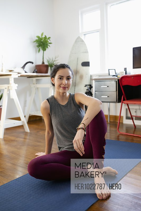 Portrait confident young Latinx woman on yoga mat in apartment