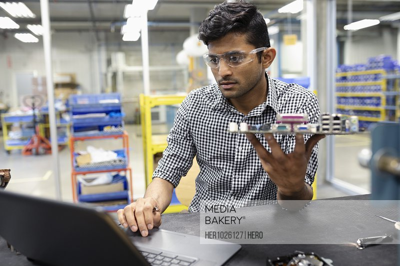 Focused male engineer assembling circuit board at laptop in research lab