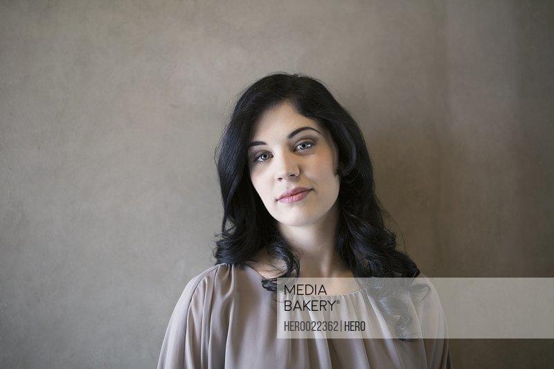 Portrait confident woman black hair against gray background