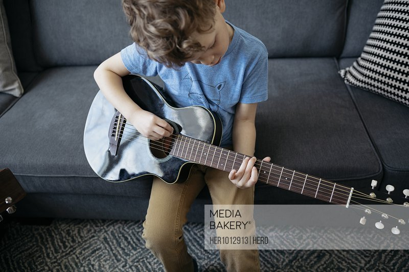 Focused boy learning to play guitar on sofa