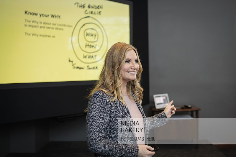 Smiling businesswoman leading conference presentation