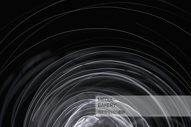 Creative, abstract spinning white spark on black background