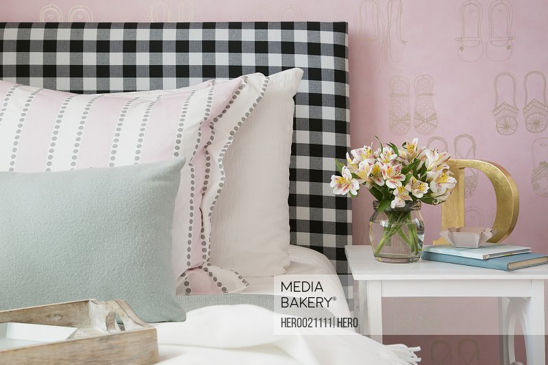 Pastel pillows on bed with gingham headboard