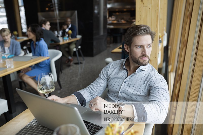 Thoughtful businessman at laptop looking out restaurant window