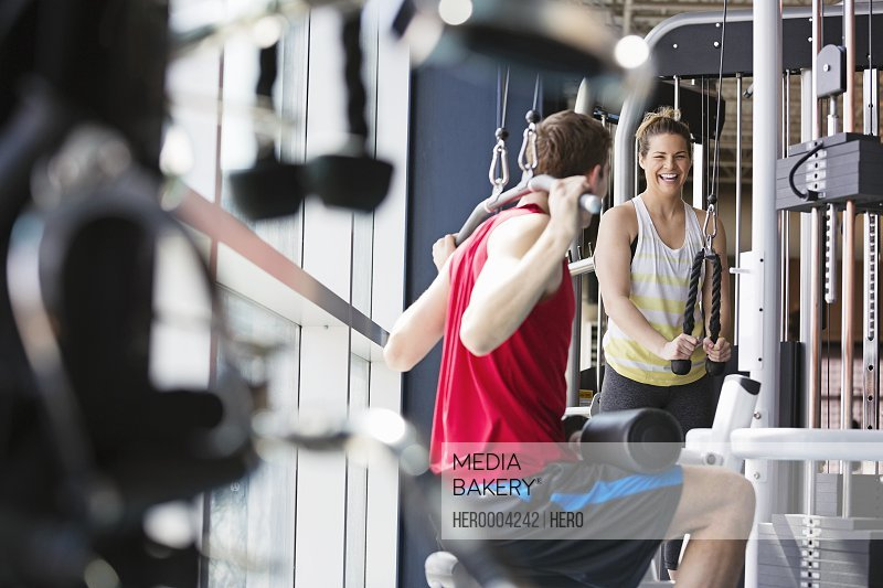 Two people using weight machines in fitness center