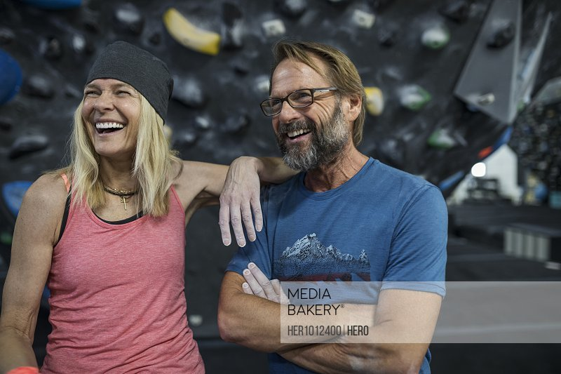 Happy mature couple rock climbers laughing at climbing gym